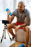 Starker Mann, der Videoblog grauer T-Shirt Schmierfilmbildung über Bodybuilding trägt stockfotos