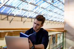 Starker Mann, der zum Treffen des Partners, unter Verwendung des Notizblockes und des Netzbuches sich vorbereitet lizenzfreie stockfotos