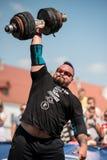 Starker Mann hebt schweren Dummkopf mit einer Hand an den Wettbewerben, Ukraine, 2017 an Stockfoto