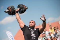 Starker Mann hebt schweren Dummkopf mit einer Hand an den Wettbewerben, Ukraine, 2017 an Stockbild