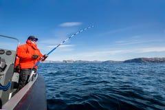 Starker Mann mit einer spinnenden Stange in seinen Händen Seeboot fisherm Lizenzfreie Stockfotografie