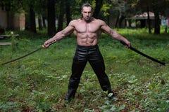 Starker Mann mit Samuraiklinge Stockfotos