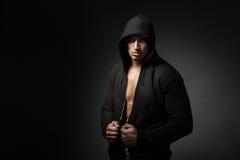 Starker Mann tragender Hoodie lokalisiert auf schwarzem Hintergrund Lizenzfreies Stockbild