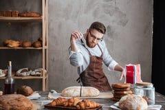 Starker Mannbäcker, der an der Bäckerei nahe Brot steht lizenzfreie stockbilder