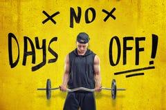 Starker muskulöser junger Mann in der schwarzen Sportkleidung, die einen Barbell mit Zeichen 'KEINER FREIEN TAGE 'auf gelbem Hint lizenzfreie stockbilder