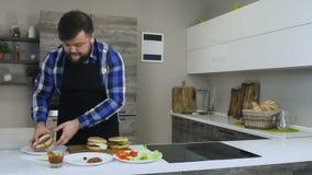 Starker oder fetter bärtiger Mann Timelapse kocht einen selbst gemachten Burger in einer Küche stock video