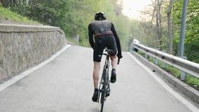 Starker Radfahrer, der das schwarze Ausstattungsreiten ansteigend aus dem Sattel heraus tr?gt Radfahrentraining Rennrad Langsame  stock footage
