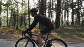 Starker Radfahrer, der Fahrrad im Park f?hrt Sun-Glanz durch B?ume Seite folgen Schuss Radfahrenkonzept stock video footage