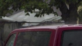 Starker Regen, der auf ein rotes Dach eines modernen Autos in der Zeitlupe fällt stock video footage