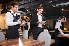 Starker Restaurantmanager, der on-line-Aufzeichnungen auf Tabelle überprüft stockfotos