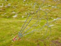 Starker Riemen und Schrott im grünen Yard, Eisen verdrehten das Seil, das durch Schraubenkarabinerhaken und -gummimuffen am Anker lizenzfreie stockfotografie