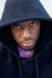 Starker schauender schwarzer Kerl mit Haubensweatshirt Lizenzfreie Stockbilder