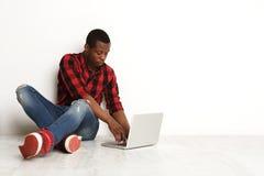 Starker schwarzer Mann, der den Laptop sitzt auf dem Studioboden verwendet Lizenzfreies Stockbild