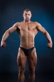 Starker Sitzmann, der seine leistungsfähigen Muskeln demonstriert Stockbild