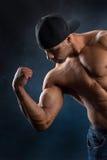 Starker Sitzmann, der seine leistungsfähigen Muskeln demonstriert Stockfotos
