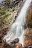 Starker sonnenbeschiener Wasserfall, der auf dem Felsen herstellt einen Regenbogen spritzt Stockfotografie
