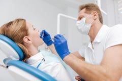 Starker talentierter Zahnarzt, der zahnmedizinische Überprüfung durchführt Stockfotos