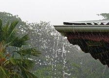 Starker tropischer Regen an einem Hausdach stockbild