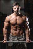 Starker und hübscher athletischer junger Mann mischt ABS und Bizeps mit stockbilder