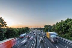 Starker Verkehr der Sonnenuntergangansicht, der mit Geschwindigkeit auf BRITISCHER Autobahn in England sich bewegt stockfotografie