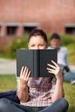 Starker weiblicher Kursteilnehmer, der ein Buch im Freien liest Stockfoto