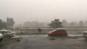Starker Wind, reißend oder Sturm auf Stadtstraße Leistungsfähige Jets des Regenfalles auf den Asphalt Bewegen und parkendes Auto stock video footage