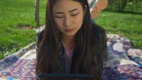 Starkes asiatisches Mädchen, das an Tabletten-PC im Park arbeitet stock footage
