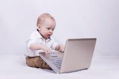 Starkes Baby, das auf Laptop spielt oder programmiert Konzept von neuem es Generation Stockfoto