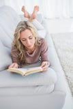 Starkes blondes Lügen auf Couchlesung Lizenzfreie Stockfotografie