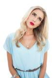 Starkes blondes Modell im blauen Kleid, das weg schaut Lizenzfreie Stockfotos