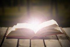Starkes Buchlügen offen auf Holzoberfläche, glühender lebhafter Sternstaub, der, schöne Nachtlichteinstellung, Magie herauskommt Lizenzfreies Stockbild