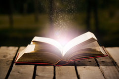 Starkes Buchlügen offen auf Holzoberfläche, magischer Sternstaub, der aus sie, schöne Nachtlichteinstellung, Magier herauskommt Stockbild