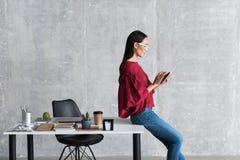 Starkes elegantes Mädchen liest Nachrichten lizenzfreie stockfotografie