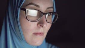Starkes Gesicht der moslemischen Frau im hijab und der Gläser nachts in den dunklen Suchen das Internet stock video footage