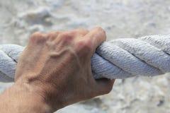 Starkes großes gealtertes Seil des Mannhandzupacken-Griffs Lizenzfreie Stockfotos
