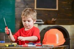 Starkes Kind, das mit Schraubenzieher spielt Netter blonder Junge, der lernt, mit Werkzeugen zu arbeiten Ergreifungsschraube des  Lizenzfreies Stockfoto