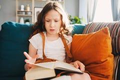 Starkes Kindermädchen, das zu Hause interessantes Buch liest Stockbild