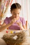 Starkes Mädchen, das bei Tisch Ostereier malt Stockfotos