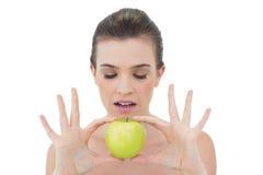 Starkes natürliches braunes behaartes Modell, das einen grünen Apfel hält Lizenzfreie Stockbilder