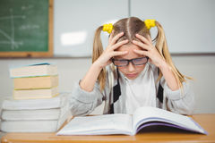 Starkes Schülerlesebuch an ihrem Schreibtisch Stockbild