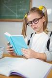 Starkes Schülerlesebuch an ihrem Schreibtisch Lizenzfreie Stockfotografie