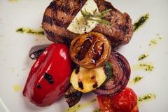 Starkes Steak mit Rosmarin und gebratenem Gemüsekäse auf weißer Platte Über Ansicht lizenzfreie stockfotos