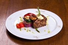 Starkes Steak mit Rosmarin und gebratenem Gemüsekäse auf weißer Platte Stockbild