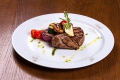 Starkes Steak mit Rosmarin und gebratenem Gemüsekäse auf weißer Platte Lizenzfreie Stockbilder