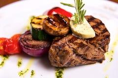 Starkes Steak mit Rosmarin und gebratenem Gemüsekäse auf weißer Platte Abschluss oben Lizenzfreies Stockfoto