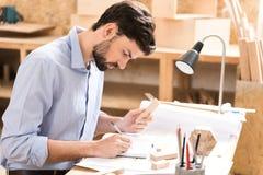 Starkes Vorlagenarbeiten der jugendlichen Schreinerei an Skizzen an seinem Schreibtisch Lizenzfreie Stockbilder