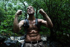 Starkes Zujubeln des Überlebensmannes im Dschungelregenwald Lizenzfreies Stockfoto