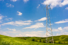 Starkstromleitung auf grünem Feld Stockbild