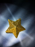 Starlight. Yellow Star on steel background Stock Photos