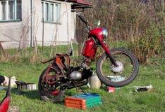 Staromodny czerwony motocykl podczas utrzymania Jawa motocykl w ca?ej paradzie Od?wie?anie retro rower po d?ugich zim wewn?trz zdjęcia stock